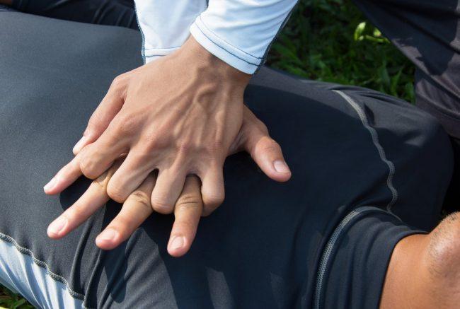 Одна рука кладется ладонью на нижнюю треть грудины, так чтобы основной упор приходился на пясть. Другая рука кладется сверху. Обе руки должны быть прямыми. Это дает возможность делать ритмичные надавливания верхней половиной тела.