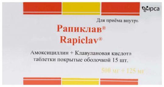 На фото таблетки покрытые оболочкой Рапиклав, Амоксициллин + Клавулановая кислота, в количестве 15 шт.
